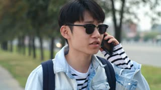 Teenage Asian boy in sunglasses standing on the street and talking on cell phone