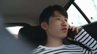 Teenage Asian boy riding in backseat in car and talking on cell phone