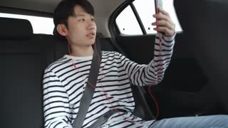 Teenage Asian boy riding in backseat in car and talking via video call on smartphone with headphones