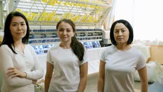 Three cheerful Asian women standing in textile factory and posing at camera while industrial machine producing fabric in the background