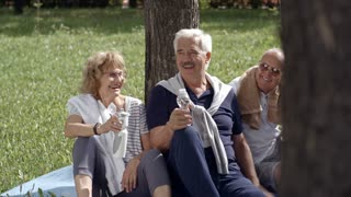 Three elderly people sitting on grass and leaning on tree after workout, drinking water from bottles and talking to each other in relaxed manner