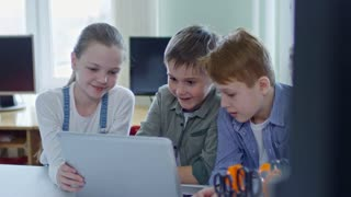 Three interested schoolchildren, two boys and one girl, talking to each other while looking at laptop computer screen in information technology class at school