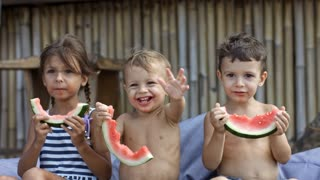 Three preschool children eating watermelon at the beach, smallest child waving hand at someone and smiling
