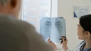Tilt down of Asian female doctor reading x-ray image of chest, speaking to patient and writing down prescription
