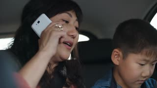 Tilt down of Asian woman talking on mobile phone and little son playing on digital tablet while riding together in car