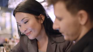 Tilt down of beautiful Asian businesswoman sitting at bar counter and discussing pictures on tablet with young male business partner