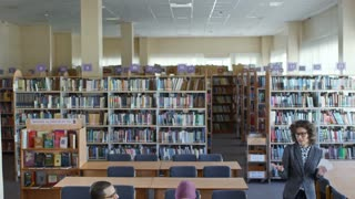 Tilt down of Caucasian female teacher giving a lecture to group of middle eastern migrants in library hall