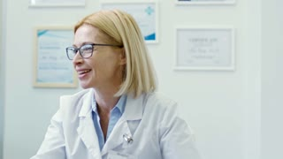 Tilt down of cheerful mature female dietician in lab coat talking and shaking hands with overweight patient