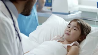 Tilt down of cute little girl lying in hospital bed and smiling while male pediatrician filling patients form on clipboard