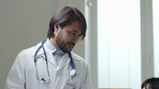 Tilt down of female Asian patient sitting in hospital bed and talking to male bearded doctor in lab coat, then taking medications from unrecognizable nurse and swallowing pills