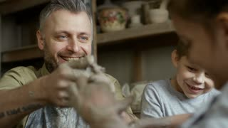 Tilt down of happy bearded man in apron throwing piece of clay on spinning pottery wheel as playful children laughing