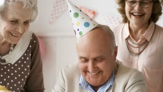 Tilt down of happy elderly man in party hat sitting at table and blowing off birthday candles on cake while friends applauding and congratulating him