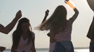 Tilt down of laughing group of friends  dancing and partying on beach on hot summer day