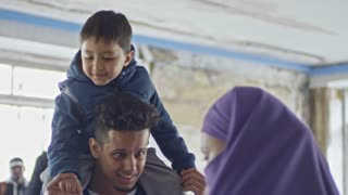 Tilt down of little boy sitting on shoulders of cheerful young Arab man chatting with unrecognizable woman in purple niqab