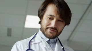 Tilt down of male Asian doctor in lab coat smiling and talking with female senior patient lying in hospital bed