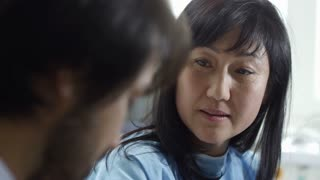 Tilt down of male doctor discussing treatment plan with female Asian patient while unrecognizable nurse with stethoscope measuring her arterial blood pressure