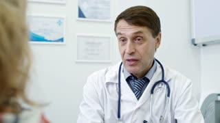 Tilt down of male physician reading information on glucose meter and talking to overweight patient