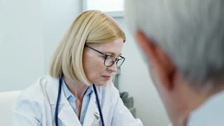 Tilt down of mature female physician checking pulse of senior man during appointment