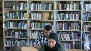 Tilt down of middle eastern woman in hijab writing in notebook at desk and listening to teacher at lesson in public library