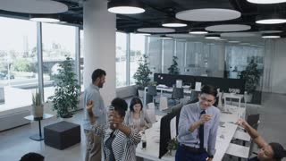 Tilt down of multi-ethic business team drinking champagne while having party during workday in open space office with panoramic window; joyous African woman dancing with colleague and smiling