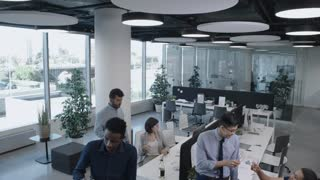 Tilt down of multi-ethic colleagues chatting, dancing and drinking champagne during workday in open space office with panoramic window