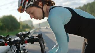 Tilt down of tired female cyclist in protective helmet inflating bicycle tires by side of road