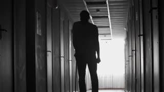Tilt down of unrecognizable figure of man with walking stick limping along dark hospital corridor