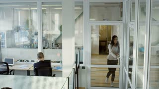 Tilt down of young Asian businesswoman walking with documents into modern open space office while employees working on computers at desks