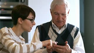 Tilt down of young woman in glasses teaching senior man how to use smartphone