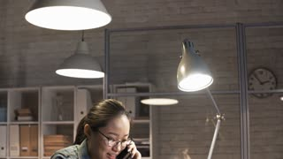 Tilt down shot of cheerful asian businesswoman speaking on mobile phone and typing on laptop at office desk in the night