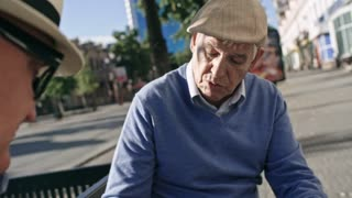Tilt down shot of elderly man sitting on bench in pedestrian street and playing chess with his friend
