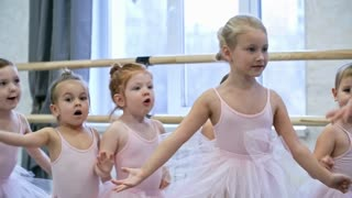 Tilt down shot of group of little girls in leotards and tutu skirts repeating dance moves after their teacher