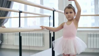 Tilt down shot of little girl in pink leotard and tutu skirt standing by ballet barre when practicing arm movements