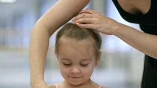 Tilt down shot of little girl in pink leotard holding hairpins while her mother is making ballet bun