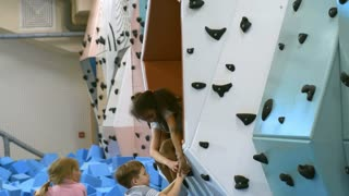 Tilt down shot of two little girls not letting friends use indoor climbing wall in children play center