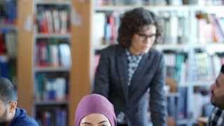 Tilt down shot of two muslim women in hijabs discussing something at desk in classroom during studying at college