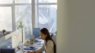 Tilt down shot of young Asian business lady sitting at desk in modern open space office in the morning and typing on laptop