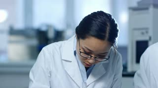 Tilt down shot of young Asian woman in lab coat and glasses writing down research details when working in laboratory