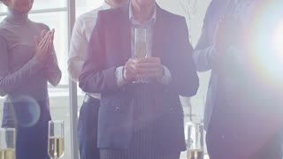 Tilt up handheld shot of smiling elderly woman holding glass of champagne at retirement party, her colleagues looking at her and clapping hands in the background