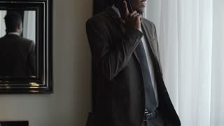 Tilt up of African businessman standing by the window in hotel room and talking on mobile phone