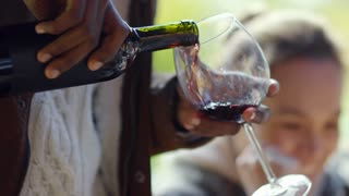 Tilt up of African man smiling and pouring red wine into the glass at outdoor party with friends