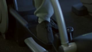 Tilt up of Arab man in sportswear using elliptical machine in gym and doing cardio workout