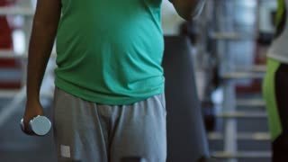 Tilt up of Arab man with a bit of extra weight doing dumbbell bicep curls exercise and looking in mirror in gym