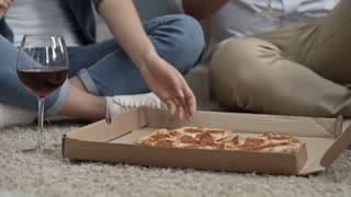 Tilt up of Asian couple sitting on floor, drinking wine and eating pizza