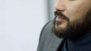 Tilt up of bearded Asian business man listening to colleague and nodding his head