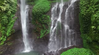 Tilt up of beautiful waterfall in green tropical forest. Drone footage