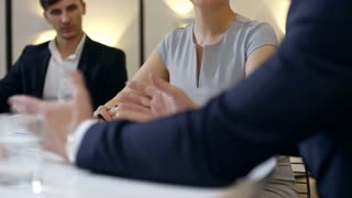 Tilt up of business man and woman sitting at office table and listening to CEO explaining something to them