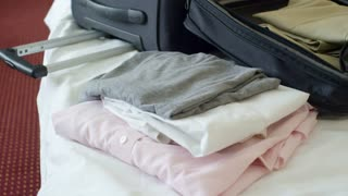 Tilt up of businessman sitting on bed with opened suitcase and clothes in hotel room and talking on the phone after arrival