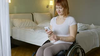 Tilt up of cheerful paraplegic woman in wheelchair laughing and chatting on mobile phone in her bedroom