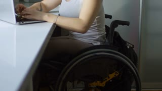Tilt up of cheerful paraplegic woman in wheelchair typing on laptop and laughing